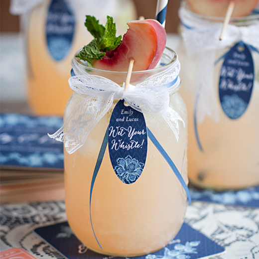 Cocktail in a mason jar with ribbon, garnish and patterned straw